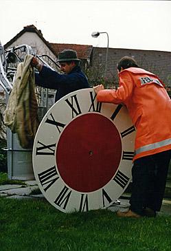Auf dem Bild ist das Ziffernblatt zu sehen, bevor es mit Hilfe der Feuerwehrleiter am Kirchturm angebracht wurde.